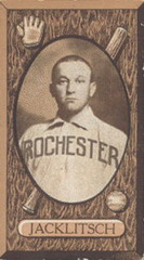 "A sepia-toned image of a man in a white baseball uniform with ""Rochester"" across the chest in dark block print"