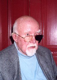 Head and shoulders of elderly man wearing glasses with one black lens. The man is white-haired and mostly bald, and sports a goatee and mustache.