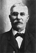 A black-and-white photograph of a moustachioed man wearing glasses and a suit and tie.