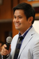 A close angle image of Alcasid smiling with a hand-held microphone in his right hand