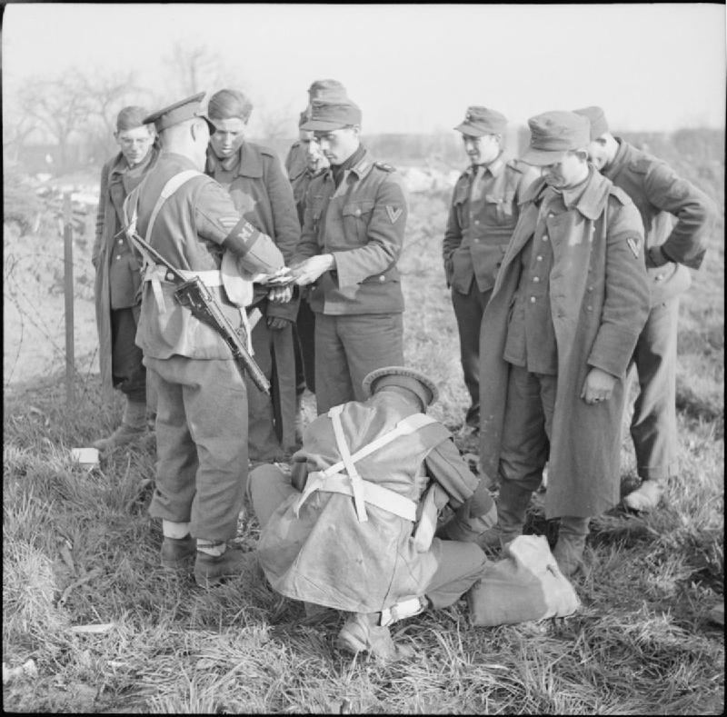 Military police search a group of German POWs