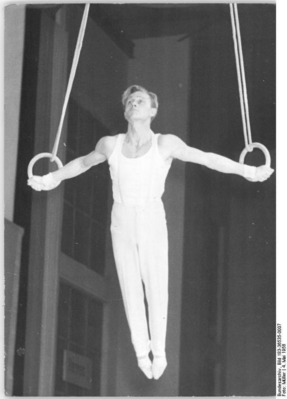 An iron cross on rings; one of the most difficult moves in men's gymnastics. You'll notice he's not muscled-out like a body builder, though.