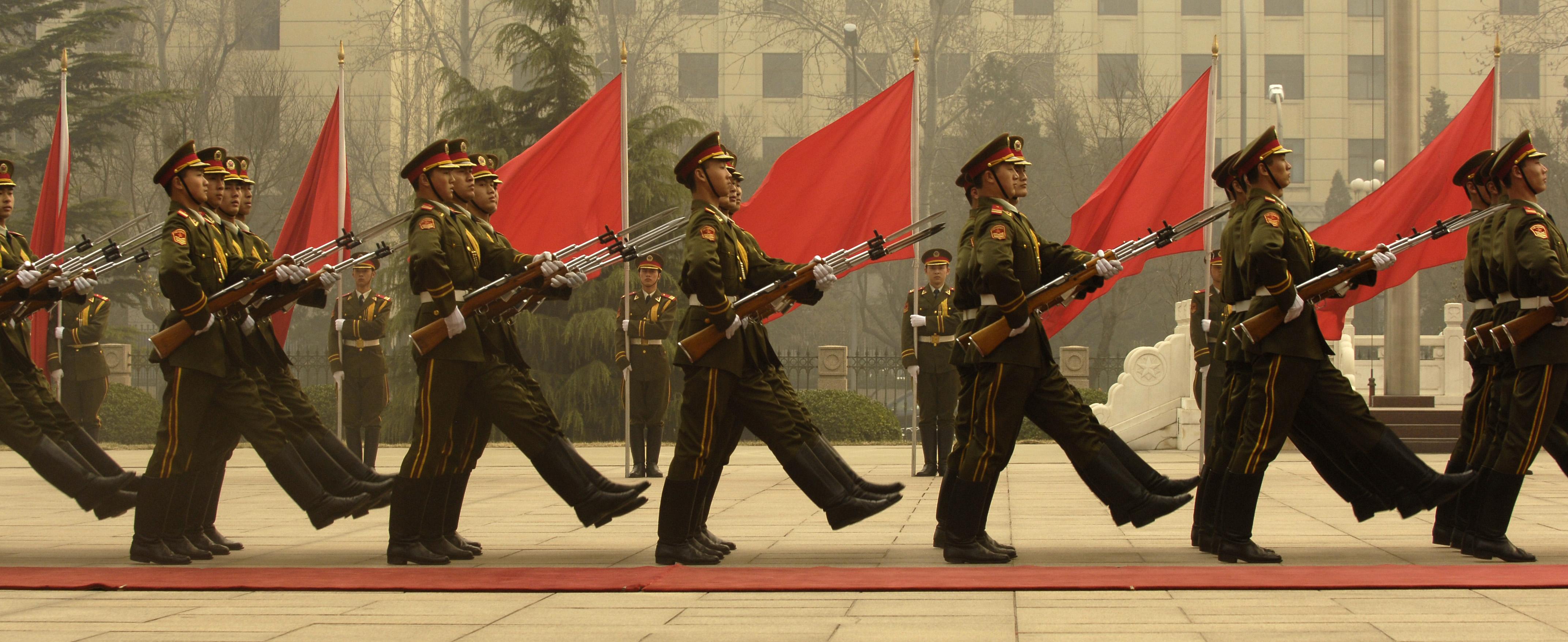 Uniform-Menschen im Gleichschritt und mit Roten Fahnen