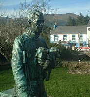 In the foreground is a dark-coloured statue of a man carrying a small dog. In the background is a low, white building with cars parked outside.