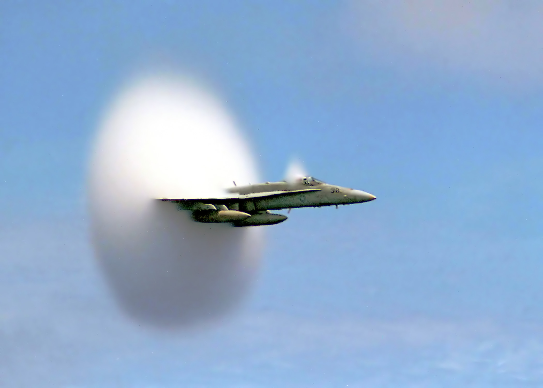 U.S. Navy F/A-18 breaking the sound barrier. The white halo is formed by condensed water droplets thought to result from a drop in air pressure around the aircraft (see Prandtl-Glauert Singularity).