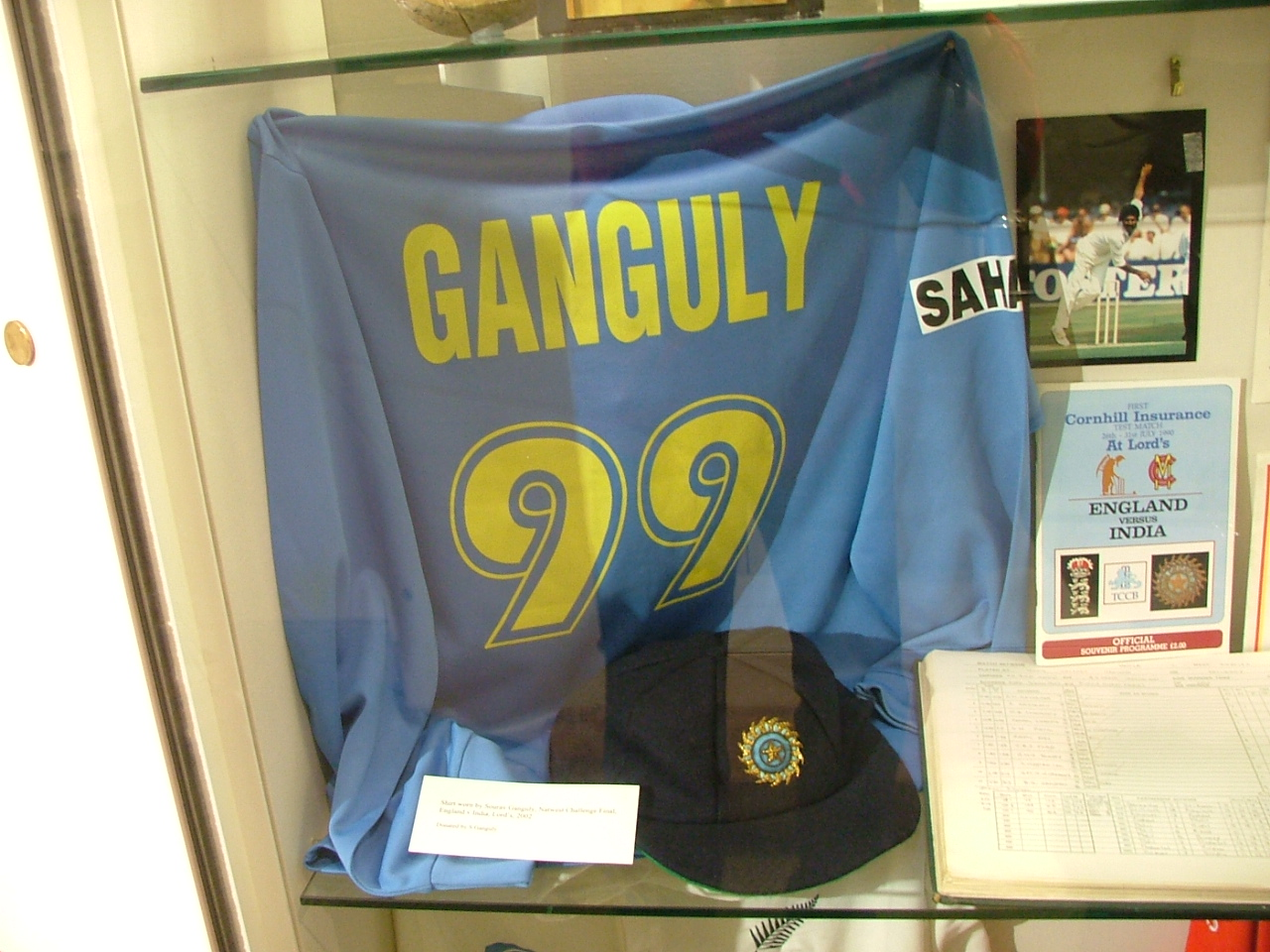 "A blue colored t-shirt displayed at a store window. The t-shirt has the words ""Ganguly"" and the number 99 below it, both in yellow color. Beside the t-shirt, a picture and an open book is visible."