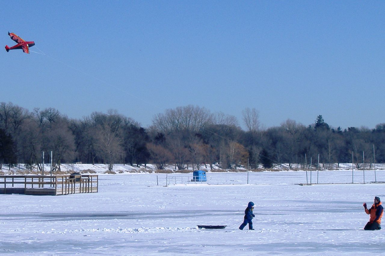 People flying kites on Lake Harriet frozen and covered with snow