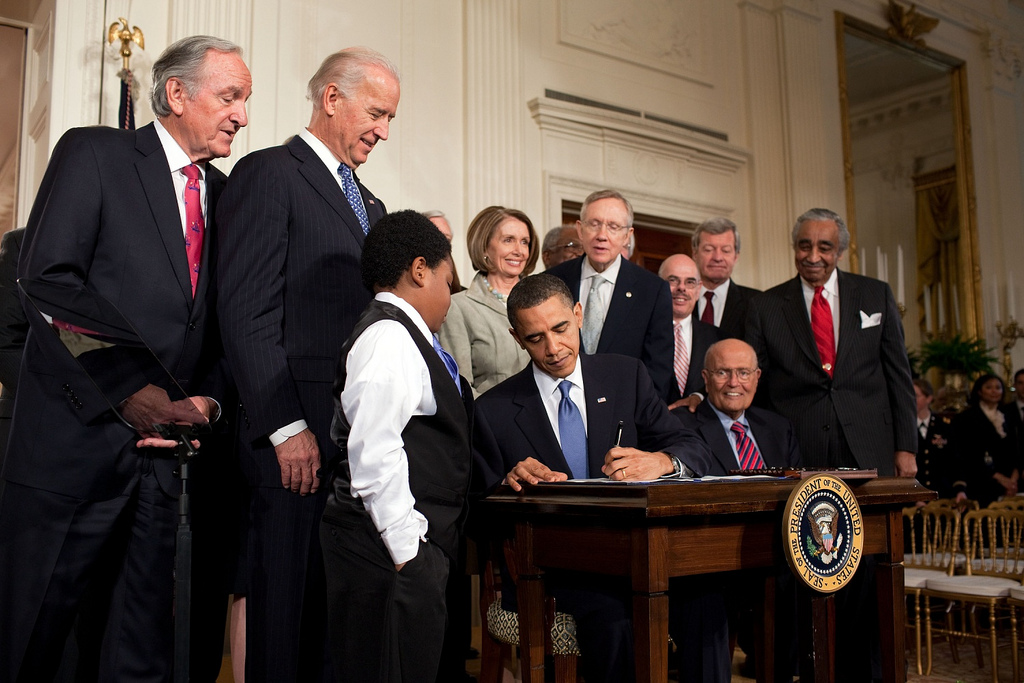 Obama signs bill at desk while others look on.