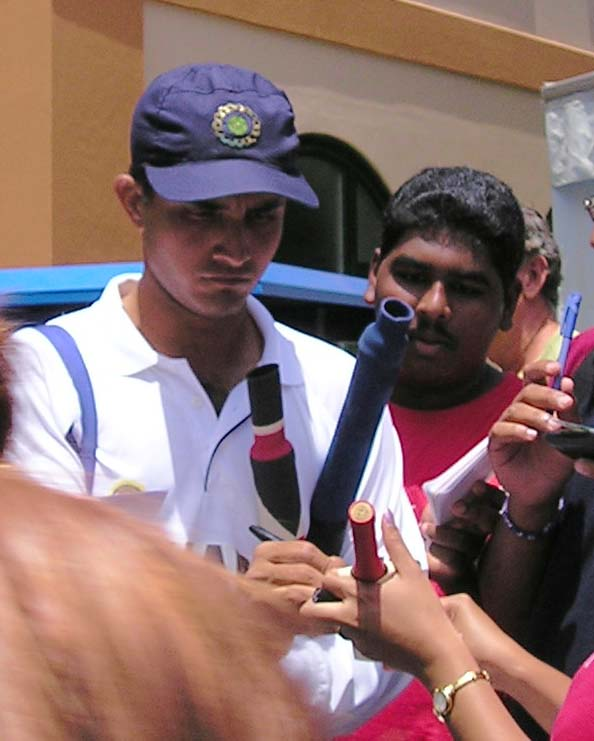 A middle-aged man signing on cricket bats. He wears a white t-shirt and a navy blue cap. A number of people are visible, who surround him.
