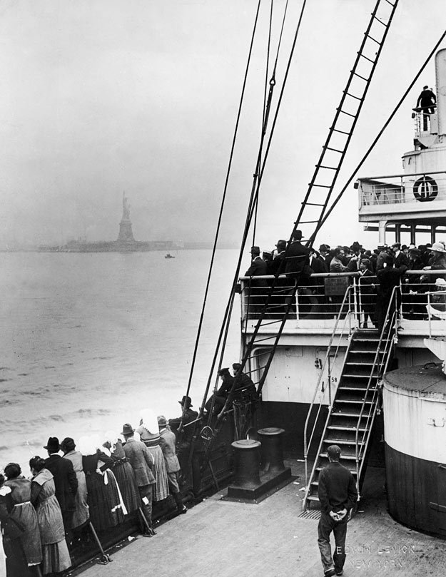 A black-and-whtie photo of passengers aboard ship look toward the Statue of Liberty