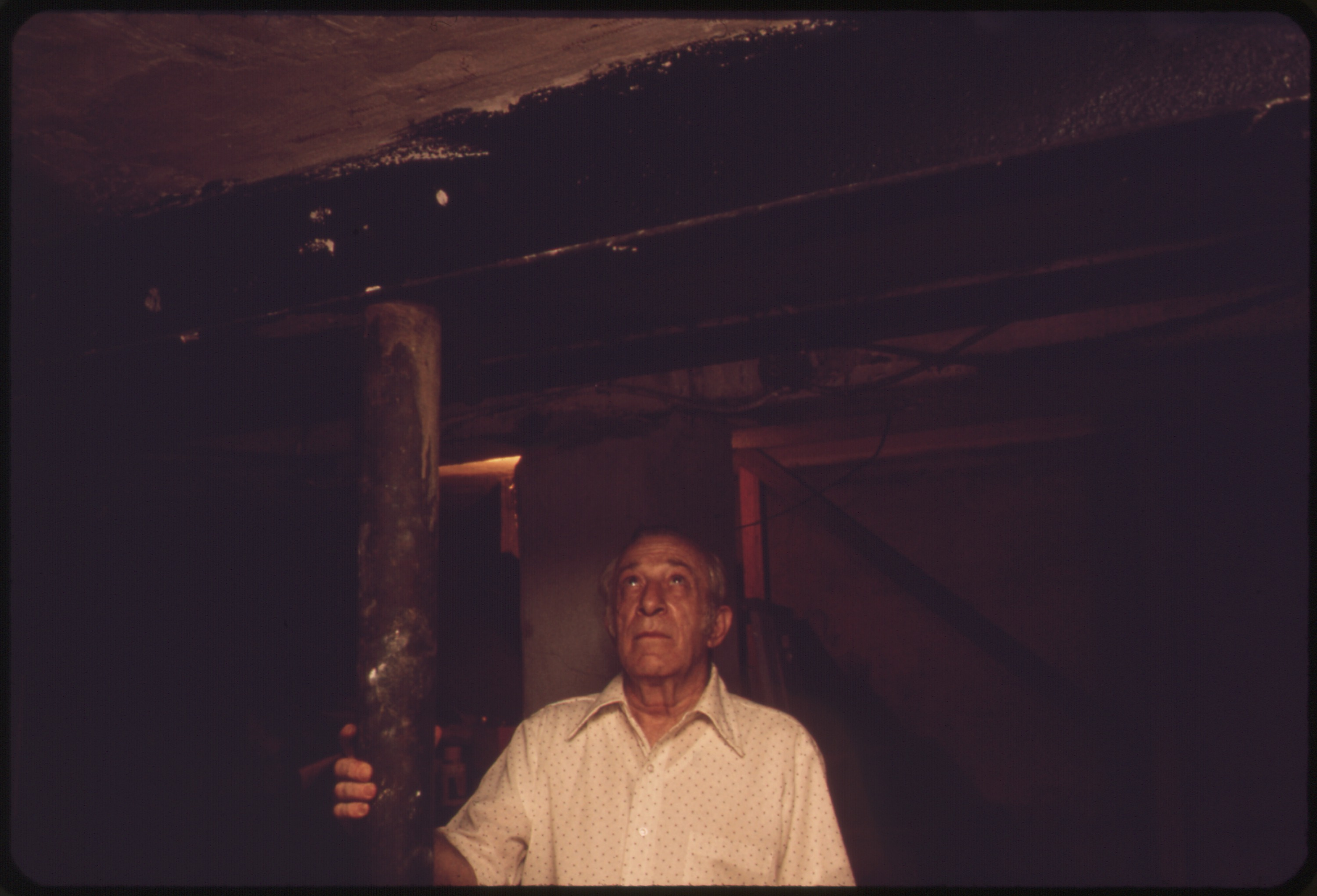 (12/02/1970 - ) Title BERNARD PICARELLO TOUCHES STEEL BEAM HE INSTALLED IN 1967 WHEN THE ORIGINAL 8X8 WOODEN BEAM (SHOWN BEHIND HIM) BEGAN TO CRACK. THE PICARELLO