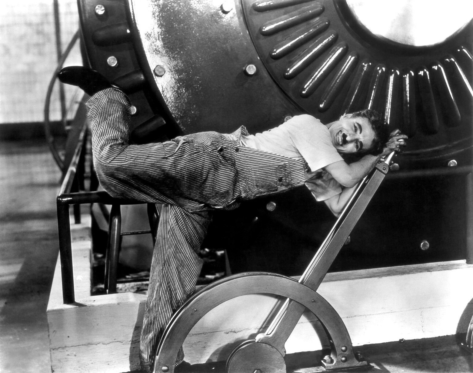Charlie Chaplin on one foot, his other kicked up behind him, as he is pulled forward by a large lever. A large piece of industrial machinery dominates the background.