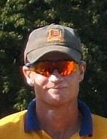 A man in a yellow shirt with a blue collar, wearing reflective sunglasses and a baseball cap, in front of foliage