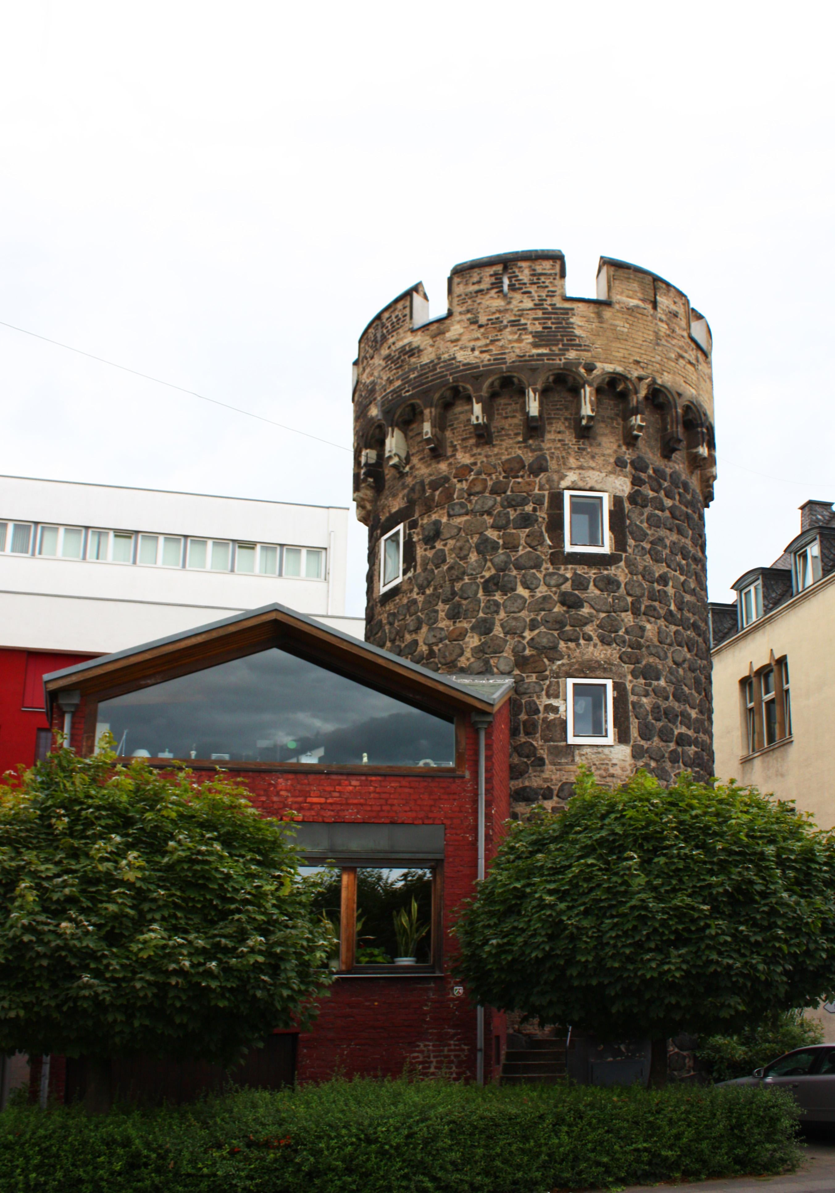 Ein kleiner Burgturm mit Zinnenkranz. Davor ein modernes, rotes Haus mit großer Glasfront.
