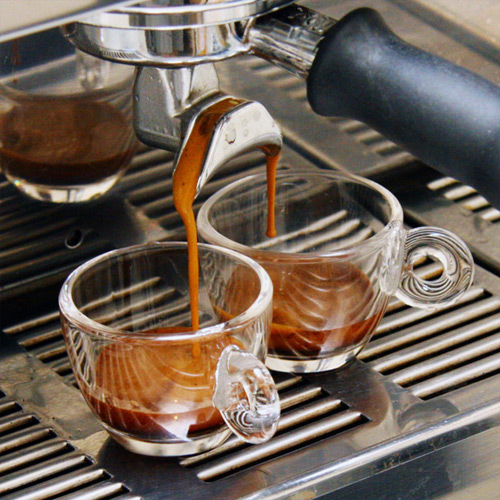 The closable pressure container has a dual outlet to dispense espresso into two cups simultaneously.