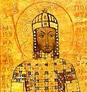 A standing male, dressed in elaborate robes with a fancy hat. He has a halo around his head and is holding a long staff in one hand.