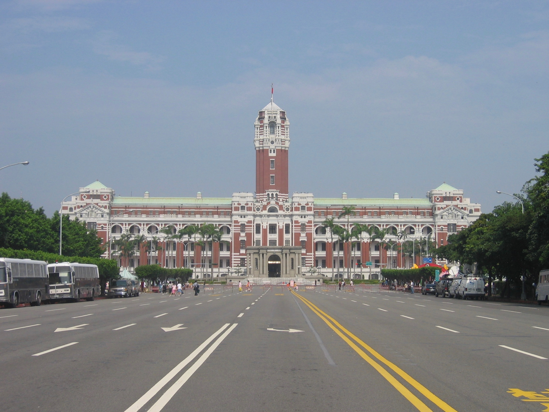 A tall and large building with a tower in its center. A large road surrounded by trees leads to it.