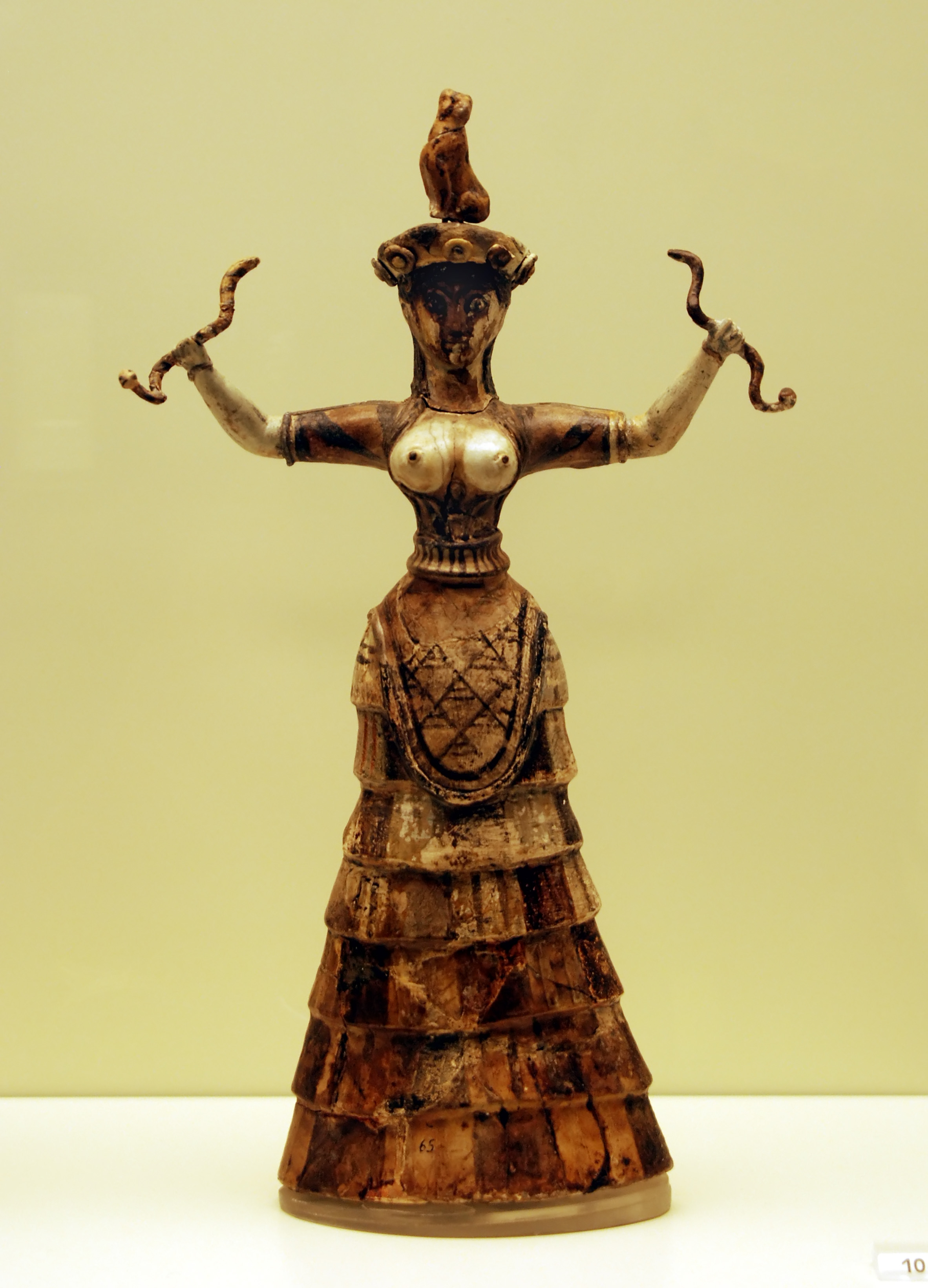 Faience figurine of the Snake Goddess from ancient Crete, with the breasts  supported by a fitted corset-like garment