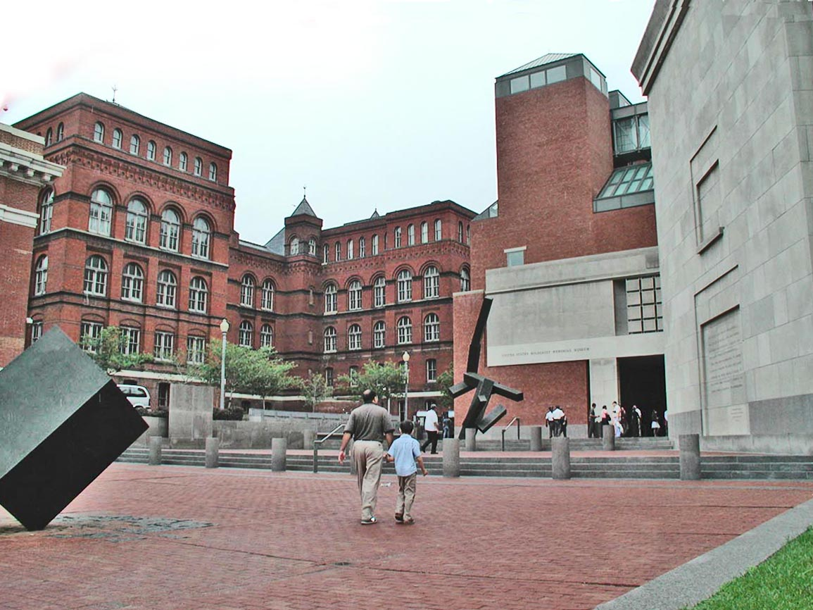 Raoul Wallenberg Place Entrance of USHMM. Three large façades made of brick and limestone. In the foreground a black modern art statue.