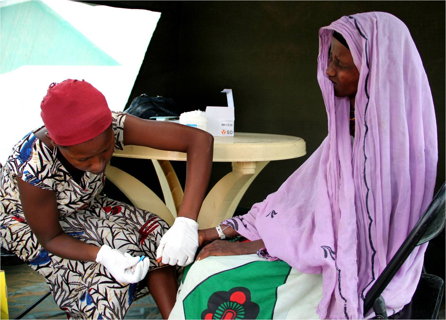 File:US Navy 110829-A-ZZ999-496 Mary Kadzo, with the organization AIDS Population and Health Integrated Assistance, draws blood from a Kenyan woman's fi.jpg
