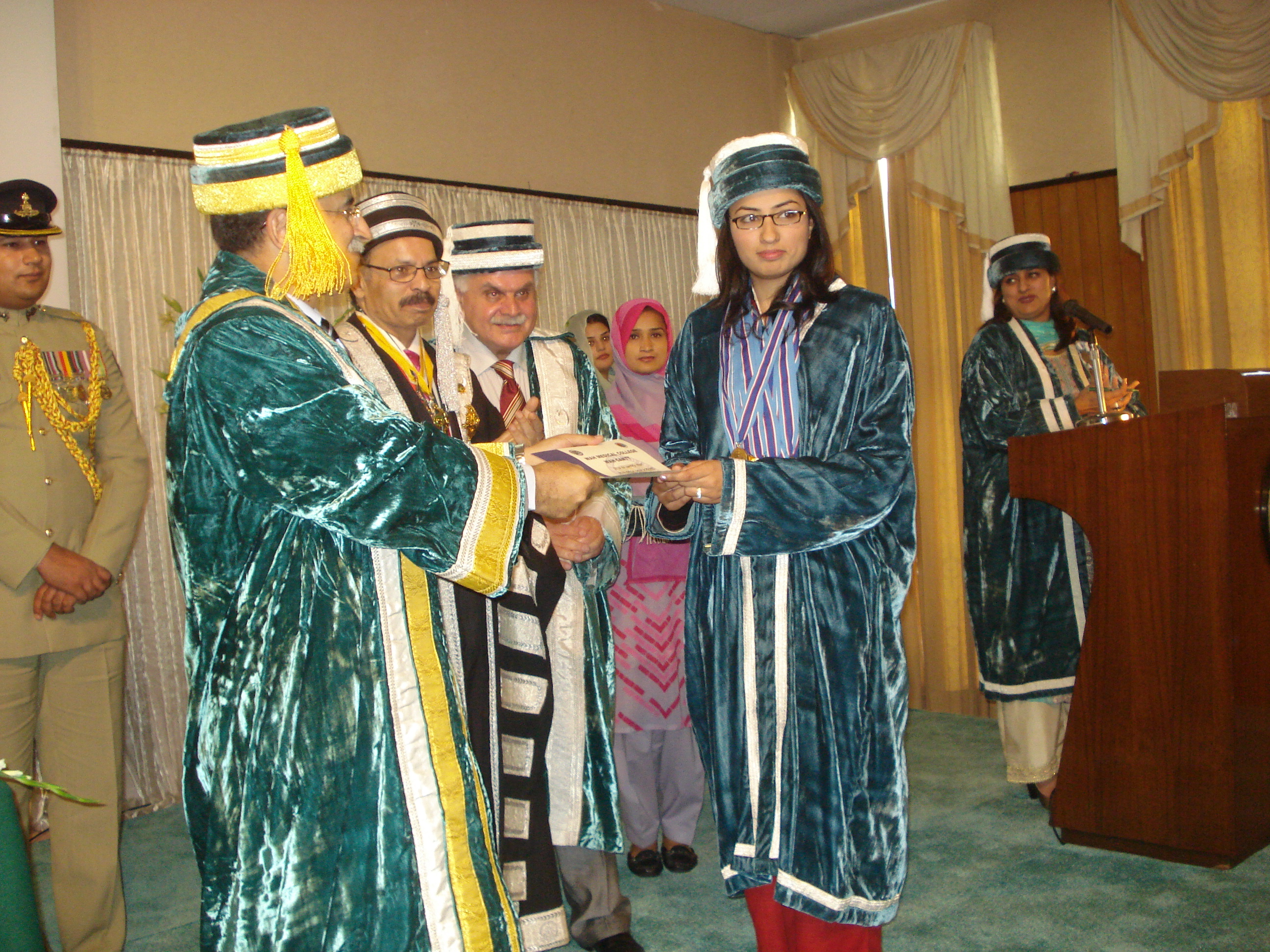 Head of college in a green crushed velvet robe trimmed in yellow and white wearing a yellow and grey fez with a long yellow tassel giving a woman in teal crushed velvet robe trimmed in white and wearing a blue, purple, and white scarf with a matching fez with a long white tassel accepting a diploma.