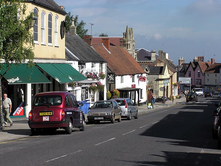 Thornbury High Street. On the left is the old market hall (now a clothes shop), the White Lion pub and a Tudor style house.