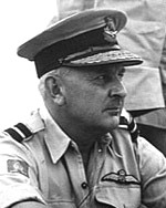 Informal portrait of a caucasian man in light-coloured military shirt with peaked cap, and pilot's wings on left-breast pocket