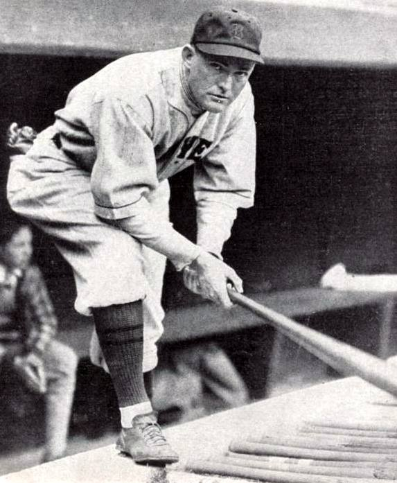Rogers Hornsby kneeling on the dugout steps.