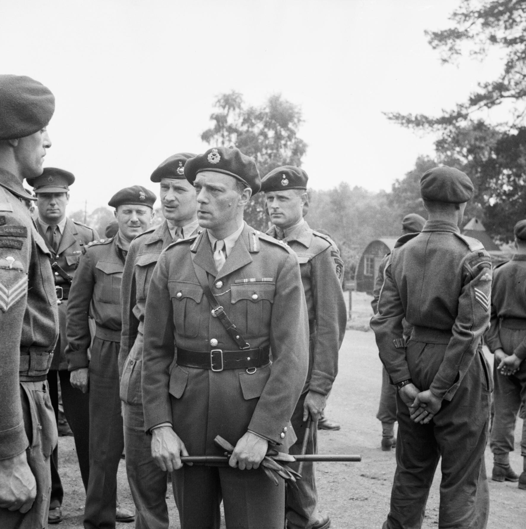 General officer with gloves and cane in hand, talking to a sergeant, surrounded by other officers and men