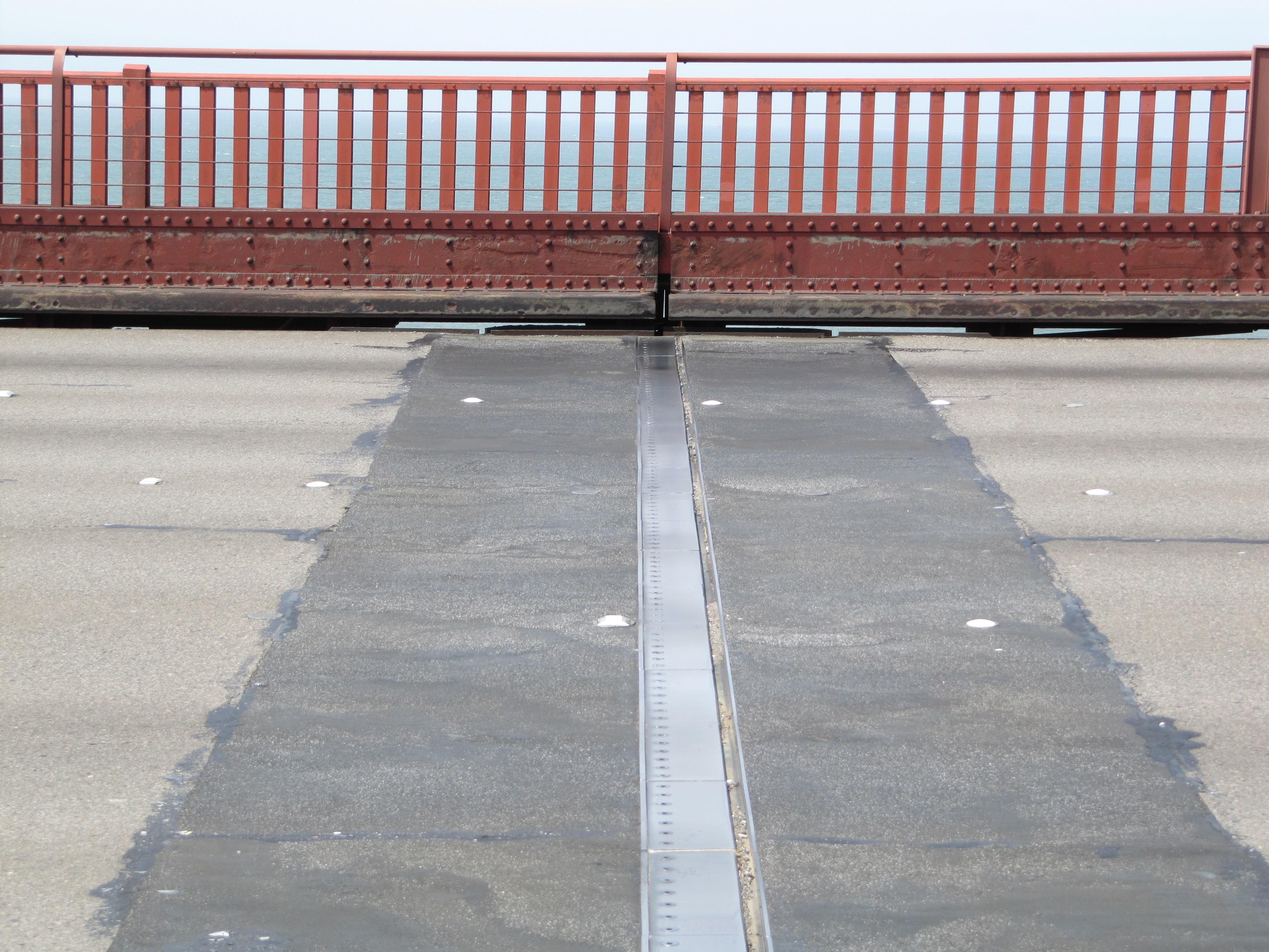 Two slabs of concrete on a bridge surface are separated by a gap covered with a metal plate that is free to slide.