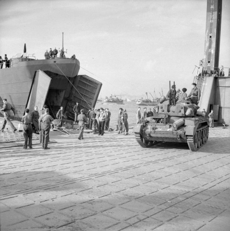 A Crusader A/A tank comes ashore from an LST