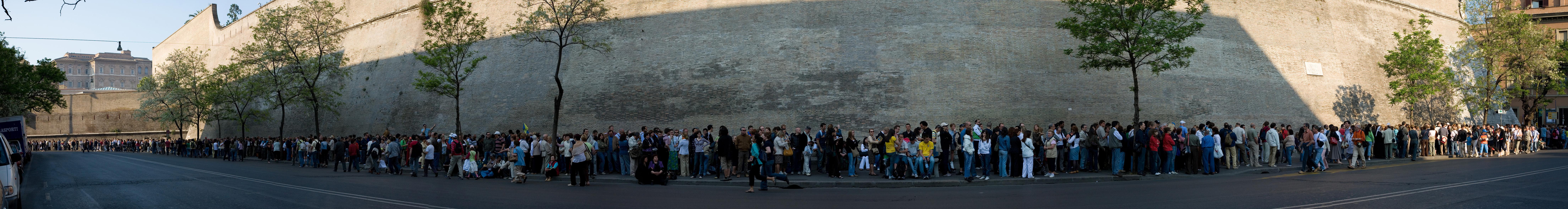 Los últimos domingos de cada mes, los Museos Vaticanos abren gratis al público. Es una oferta de mucho éxito popular y es muy común esperar colas de muchas horas para poder entrar. Las esperas son también grandes en Semana Santa. Esta imagen es una vista panorámica parcial, tomada en abril de 2007, en la que puede verse que la fila continúa en ambas direcciones, alcanzando en este caso una longitud de medio kilómetro.
