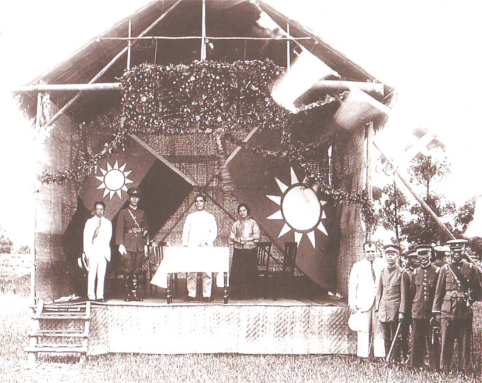 Sun Yat-sen (middle, dressed in white) and Chiang Kai-shek (on stage in uniform) at the founding of the Whampoa Military Academy in 1924.