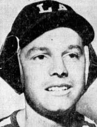 Los Angeles sportswriter Bob Hunter modeling a new baseball helmet in 1939. The helmet's design is similar to earmuffs and fits over the baseball cap.