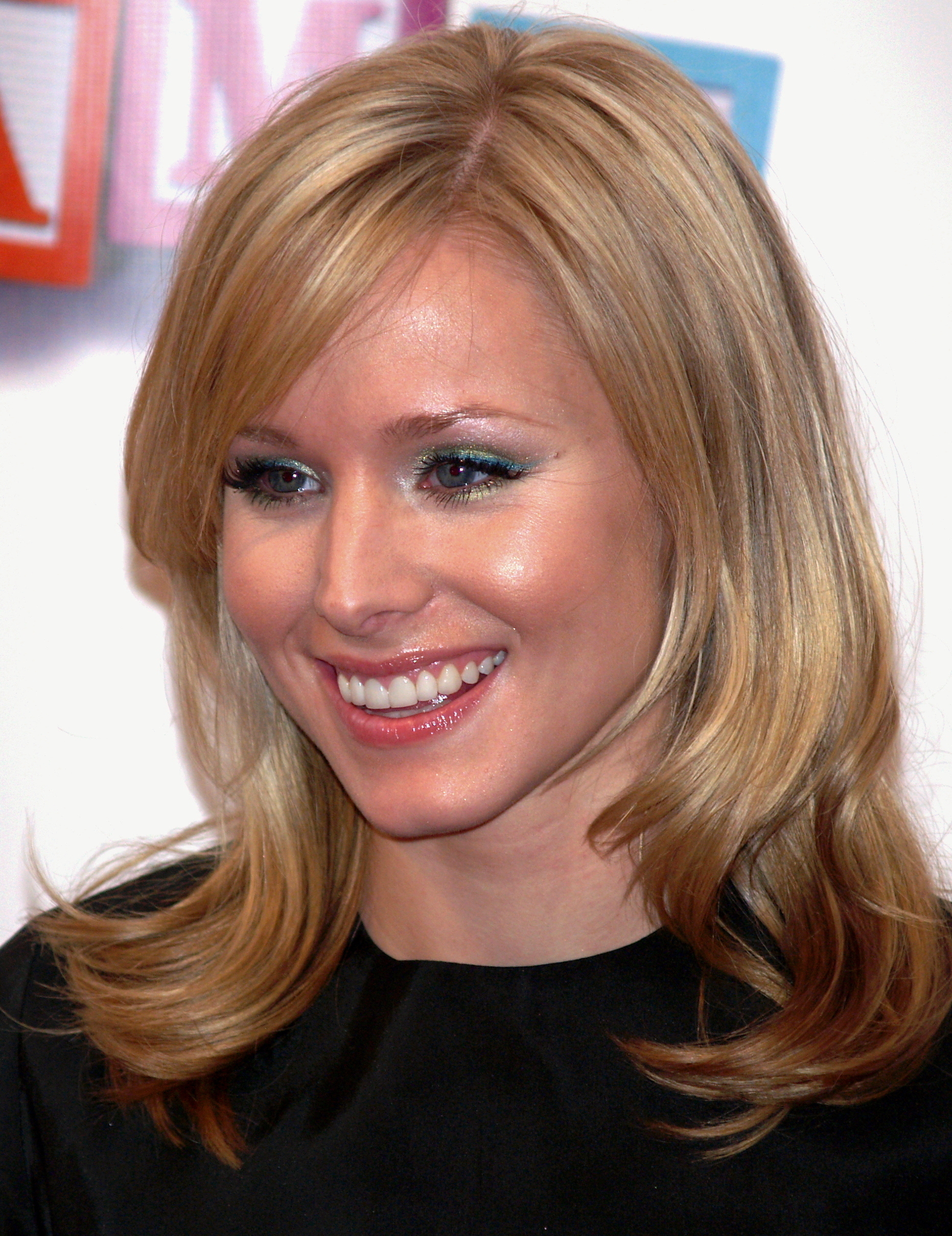Head and shoulders of young, blond woman with hair curling below her shoulders, smiling.