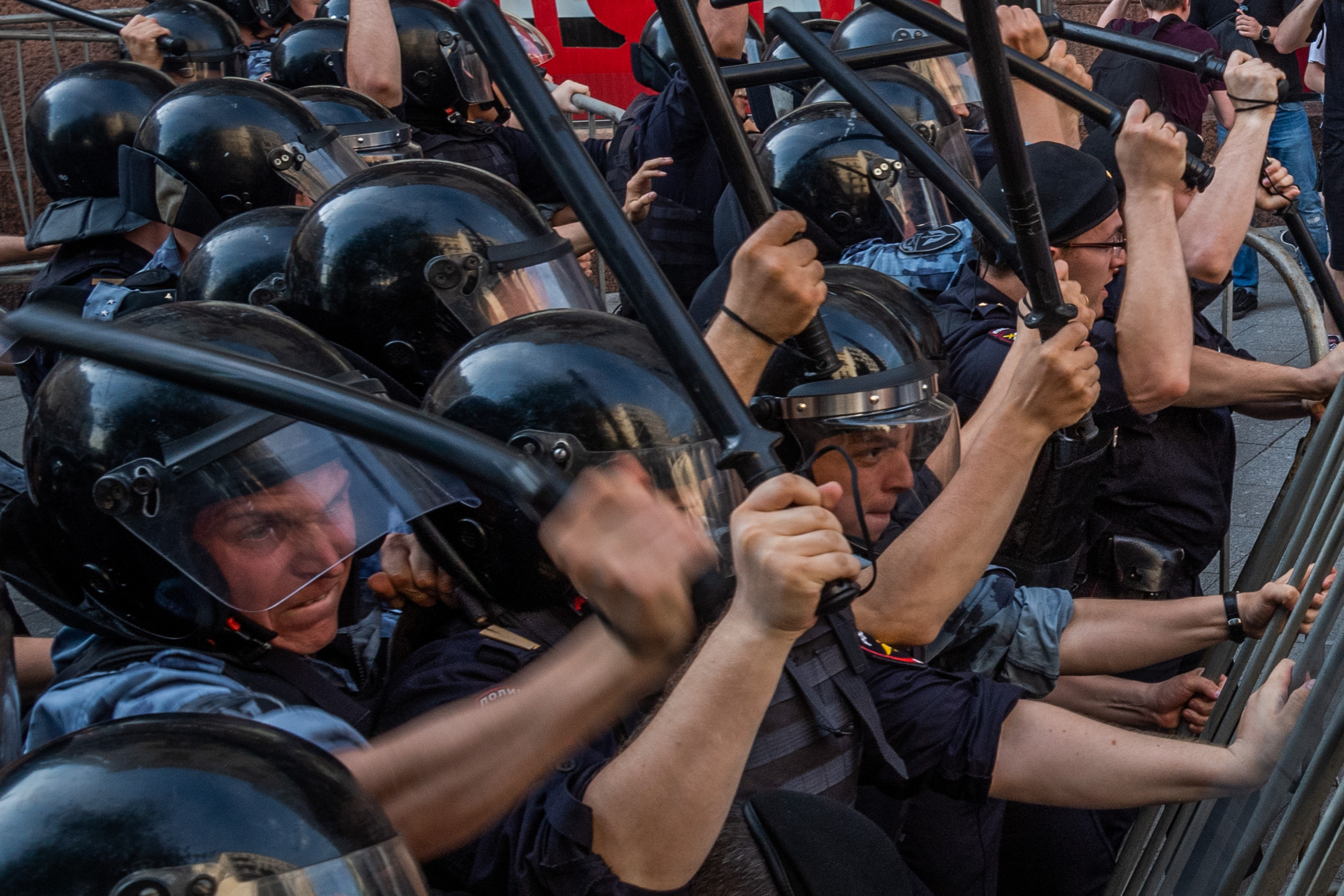 Hasserfüllte Gesichter der Polizeikräfte mit Schlagstöcken