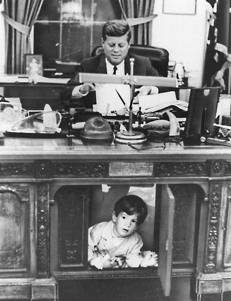 black and white image of John F. Kennedy seated at the Resolute desk with the center panel open and his young sun playing in this opening.