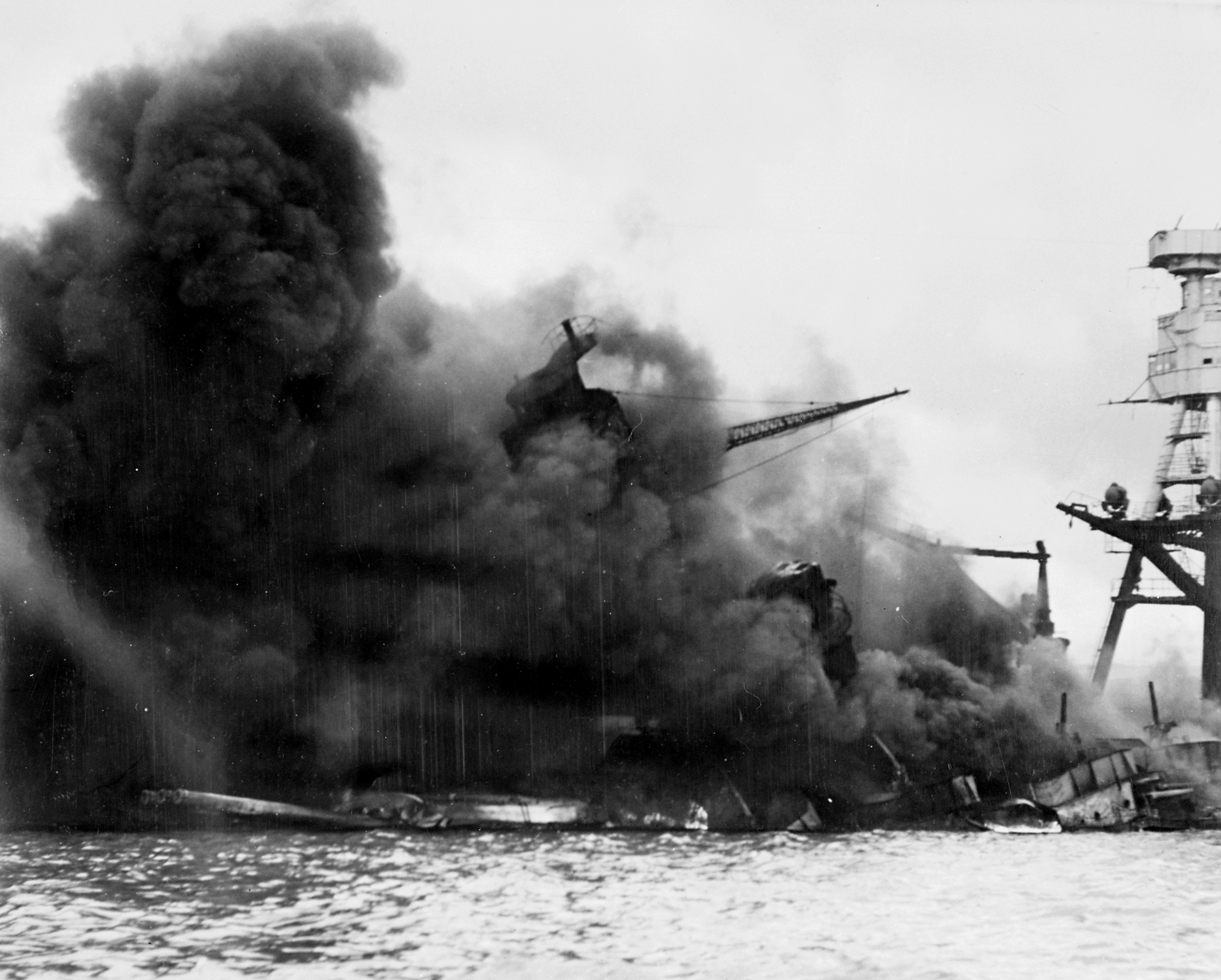 The ruined hulk of the USS Arizona burns after the attack.