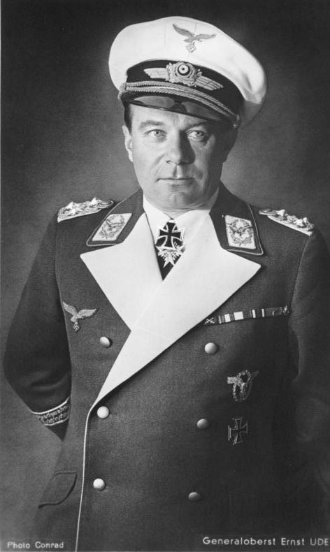 alt=The head and upper body of a man wearing a military uniform, peaked cap and various military decorations.