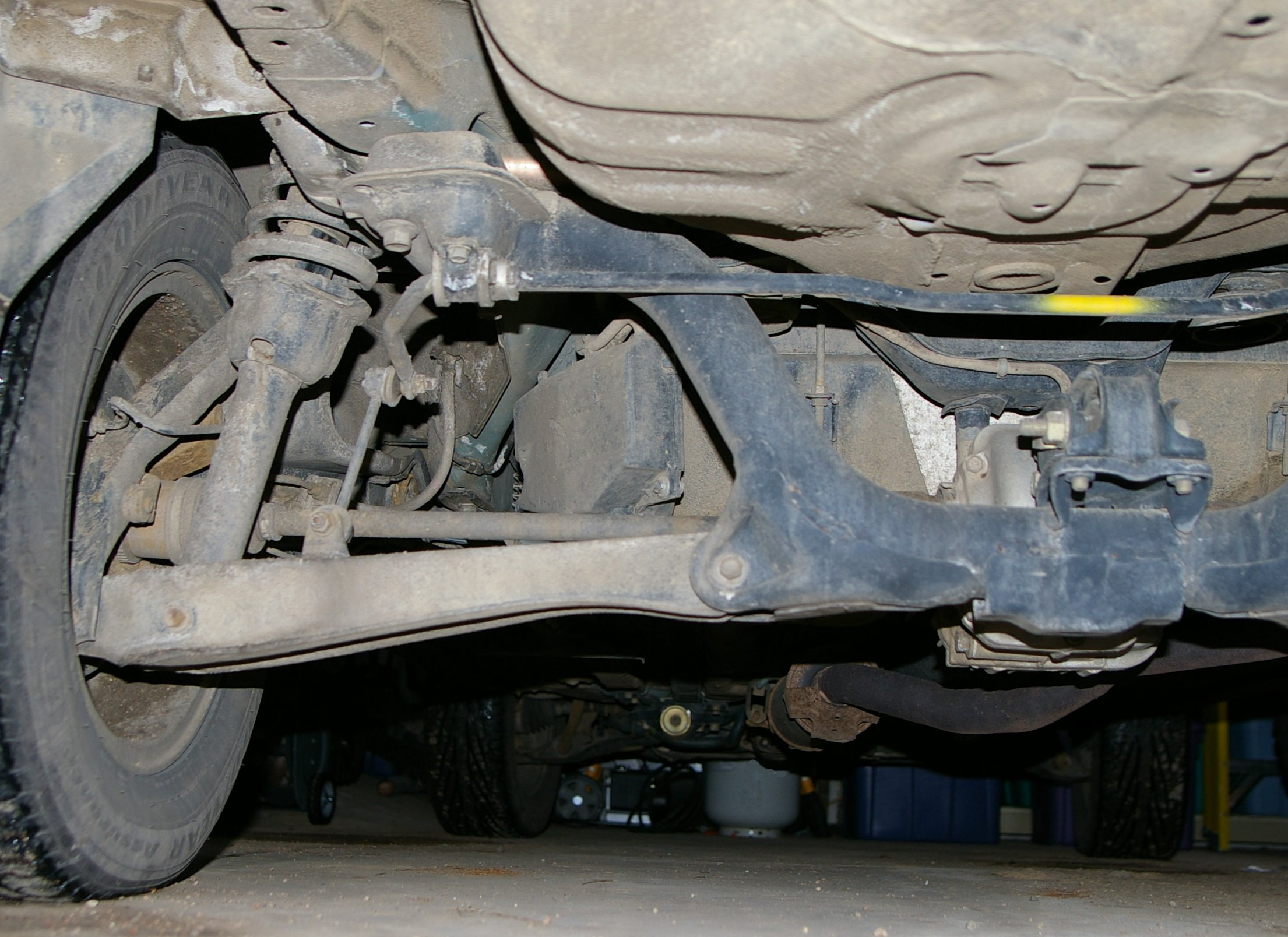 A multi-link type rear independent suspension on an AWD car. The anti-roll bar has some yellow paint on it.