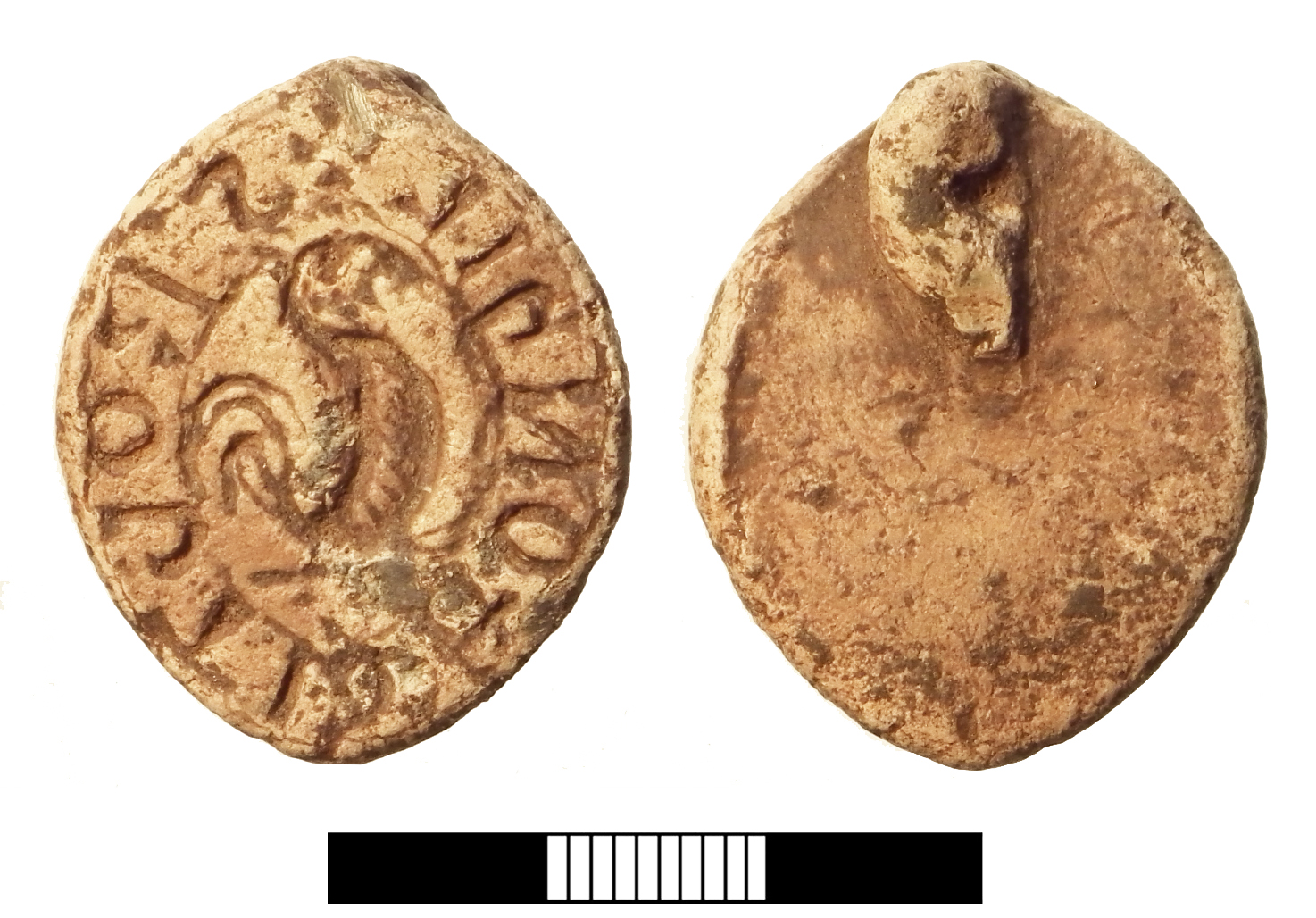 English: A Medieval lead seal matrix with a bent loop on the back at the apex. The legend reads S'RObTI DHONhIL (the surname is not fully distinct) with a standing