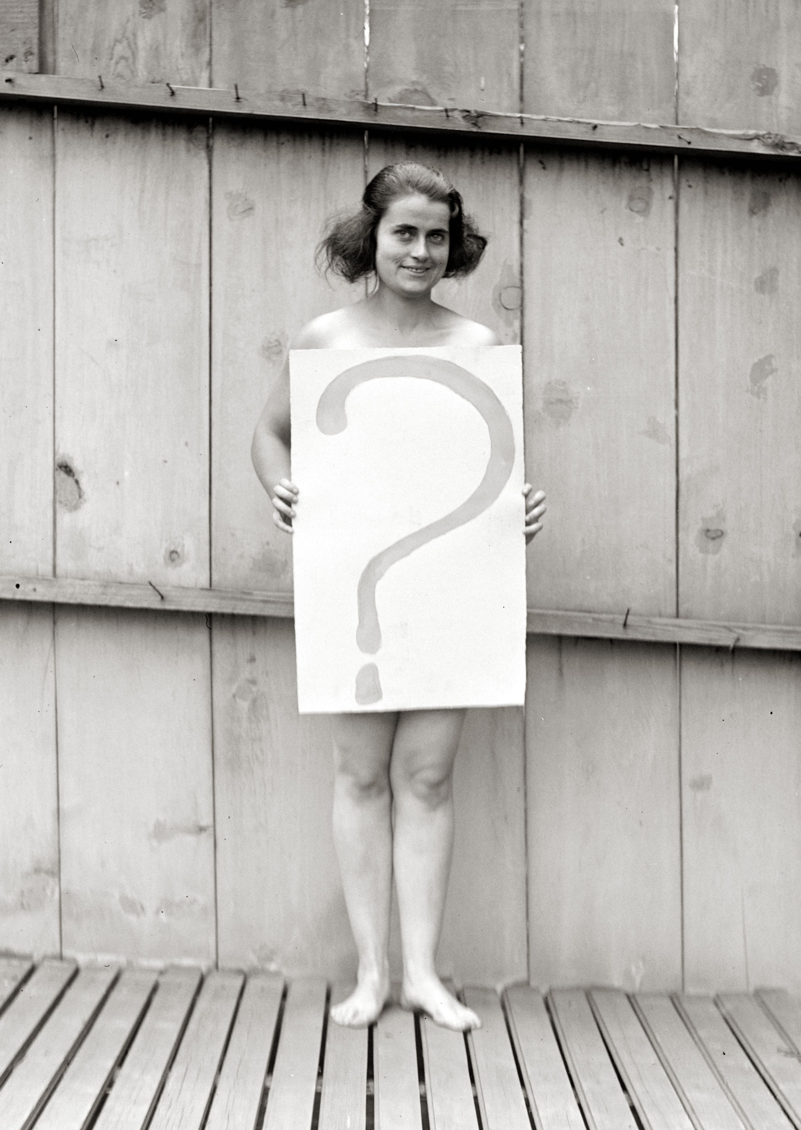 Descrizione Unclothed woman behind question mark sign.jpg