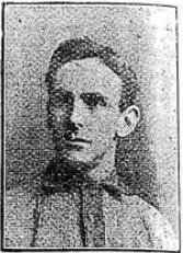 Head and shoulders of a young, clean-shaven man with dark hair parted on the left of centre. He is looking to his right, and is wearing a light-coloured sports shirt with dark collar and trim.