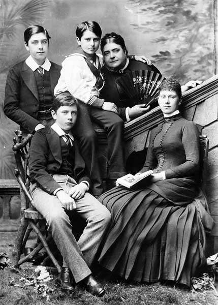 The Duchess of Teck and her family c. 1883; Prince Alexander sits centre with his arm around the Duchess, Princess Mary (later Queen Mary) is seated at far right Duchess of Teck and family colour.jpg