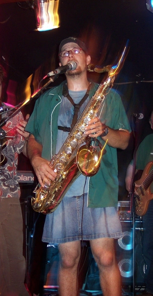https://upload.wikimedia.org/wikipedia/commons/f/ff/Guy_in_a_Skirt_playing_a_Saxophone.jpg