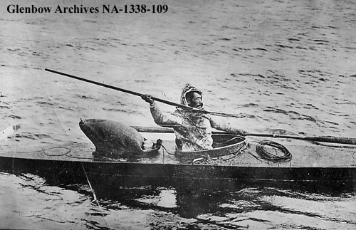 """black and white image of an Inuit hunter seated in a kayak holding a harpoon"""