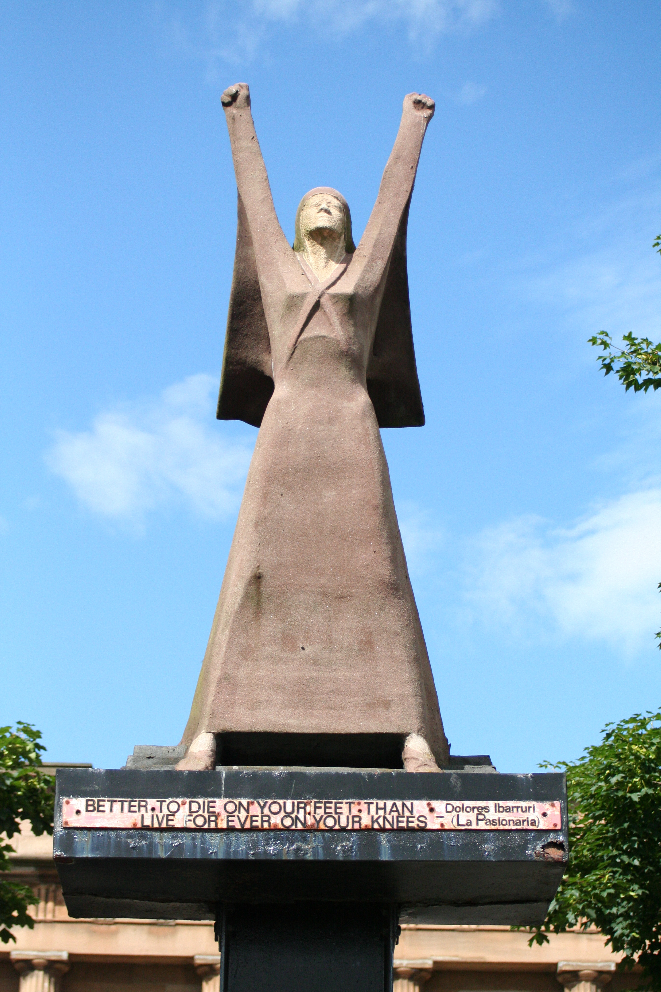 """Statue of a woman in a strong pose with both arms up in protest with fists clenched and quotation beneath """"It is better to die on your feet than to live forever on your knees."""""""