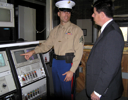 Marine Security Guard reviews the embassy%27s security alarm system with the regional security officer.jpg