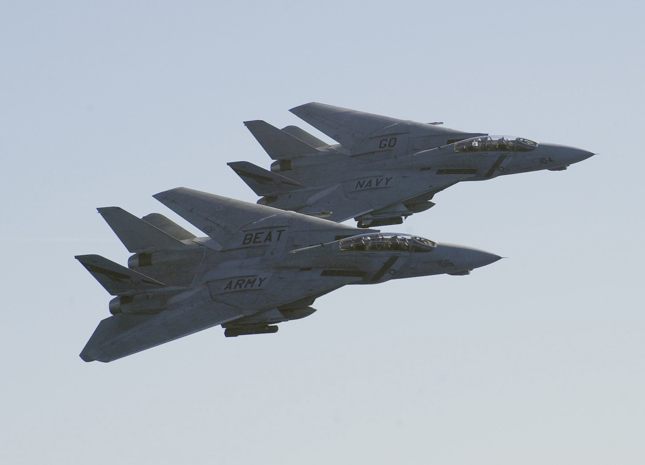 "two grey military jet aircraft in close trail formation flying by with the words ""Go Navy"" on one and ""Beat Army"" on the other"