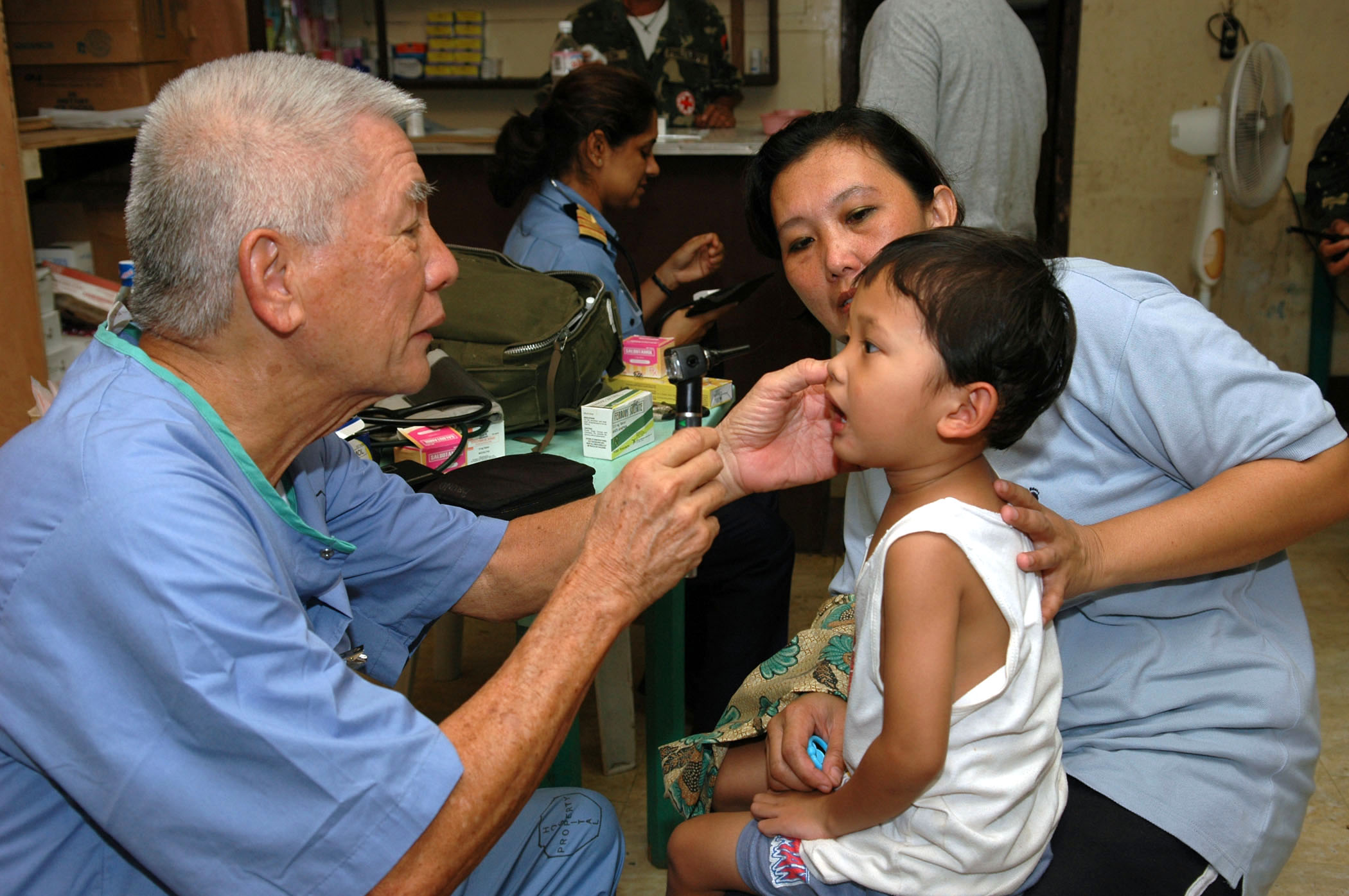 US Navy 060606-N-3714J-080 Victor Dizon, a doctor with Aloha Medical Mission, examines a boy at Camp Batista during a Medical and Dental Civil Action Project hosted by the U.S. Military Sealift Command (MSC) Hospital ship USNS.jpg